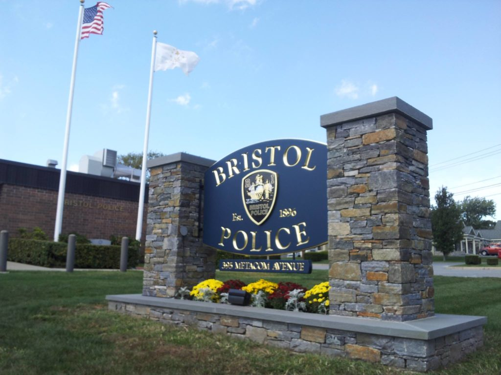 wood police department sign between 2 stone pillars